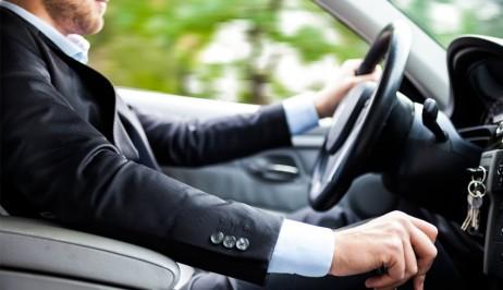 Innenaufnahme eines Autofahrers mit Anzug. Europeo Cars bietet niedrige Preise für Mietfahrzeuge auf Kreta.